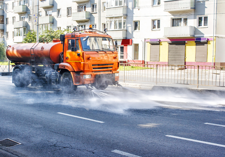 cleaning sweeper machine washes the city asphalt road with water spray on summer morning Standard-Bild