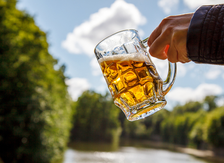 near beer: female hand holding a mug of beer near the lake on sunny summer day Stock Photo