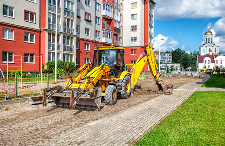 construction of a new road. excavator prepares the surface in the city on summer day Stock Photo