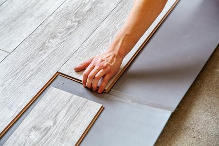 Handyman Laying Down Laminate Flooring Boards While Renovating