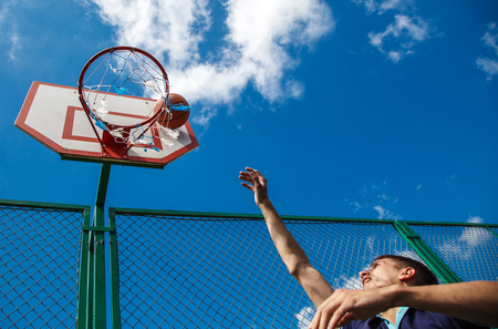young man playing basketball in the courtyard on a sunny summer day