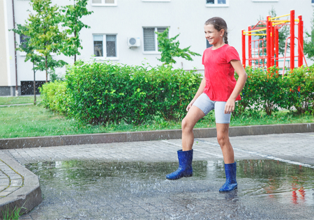 beautiful smiling girl in blue rubber boots red t-shirt and grey shorts jumping in a puddle after a rain outdoor on rainy summer day