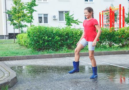 schönes lächelndes Mädchen im roten T-Shirt der blauen Gummistiefel und in den grauen Shorts, die in einer Pfütze nach einem Regen im Freien am regnerischen Sommertag springen