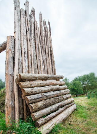 tall rough old wooden fence in the forest on gloomy summer day Imagens