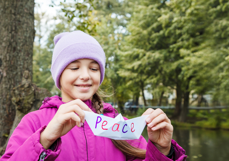 girl in blue hat and magenta jacket holding white paper boat called peace outdoor near the river on gloomy autumn day Stockfoto