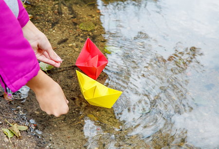 girl in magenta jacket puting two colored paper boats in the stream outdoor on autumn day. hands closeup