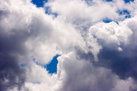 lush white cumulus clouds swim across the blue sky on a bright sunny summer day