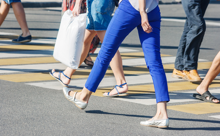 pedestrians crossing the road at a pedestrian crossing on summer sunny day Archivio Fotografico
