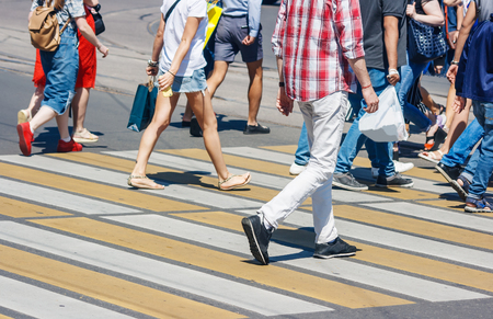 pedestrians crossing the road at a pedestrian crossing on summer sunny day Reklamní fotografie