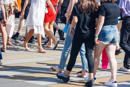 Fußgänger, die an einem sonnigen Sommertag die Straße an einem Fußgängerüberweg überqueren