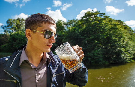 young man in sunglasses is drinking beer in the park on sunny summer day closeup