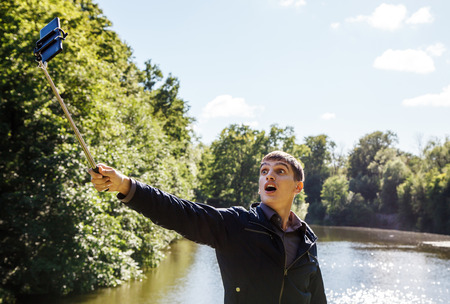 young man making selfie with a selfie stick in the park on sunny summer day closeup