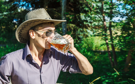young man in a cowboy hat and sunglasses is drinking beer in the park on sunny summer day closeup