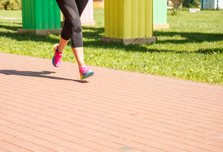 legs of girl running in a sports competition on sunny summer morning Stock Photo