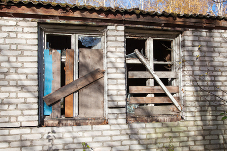 two boarded windows of an abandoned house outdoor closeup on sunny day Stock Photo