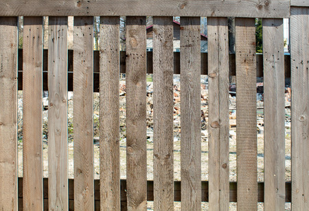 fence of rough brown boards outdoor on sunny day Stock Photo