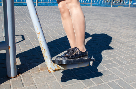 young woman is engaged on the simulator on the seafront on sunny day. legs closeup Stock Photo