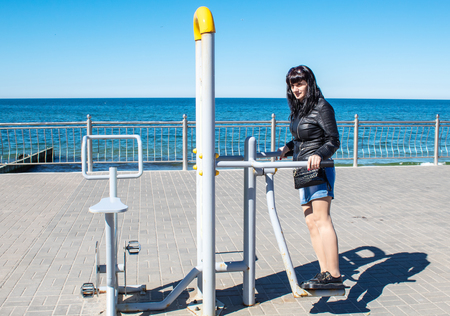 young woman in black leather jacket and blue denim skirt is engaged on the simulator on the seafront on sunny day Stock Photo