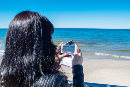 young woman using a mobile smartphone to take photo of the sea on sunny day Stock Photo