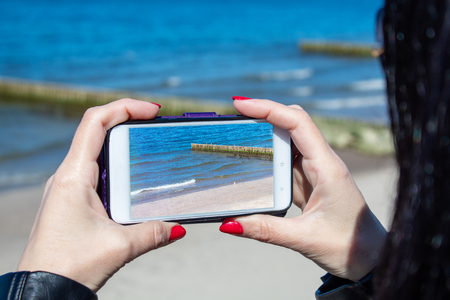 young woman using a mobile smartphone to take photo of the sea on sunny day closeup Stock Photo