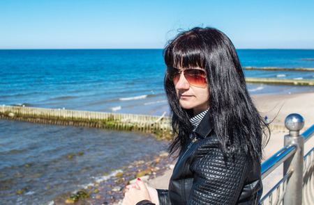 young brunette woman in black jacket and sunglasses looking at the sea walking along the shore on sunny day outdoor closeup