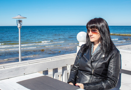 young brunette woman in black jacket and sunglasses looking at the sea sitting in the outdoor cafe on sunny day