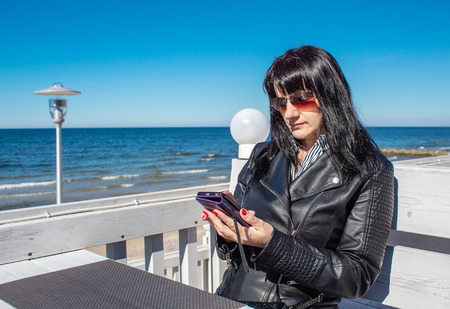 young woman using a mobile smartphone in the outdoor cafe near the sea on sunny day