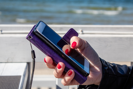 young woman using a mobile smartphone in the outdoor cafe near the sea on sunny day. hand closeup