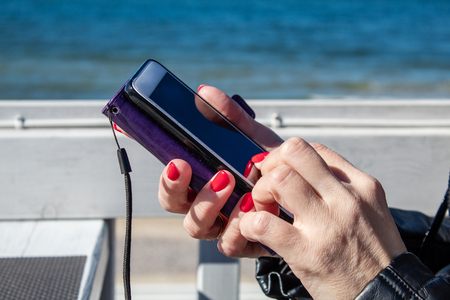 young woman using a mobile smartphone in the outdoor cafe near the sea on sunny day. hands closeup Stock Photo
