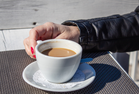 female hand holding a cup of coffee in an outdoor cafe on sunny day closeup