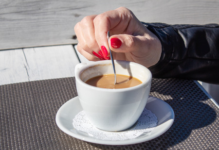 young woman in black leather jacket stirring coffee with a teaspoon in an  outdoor cafe near the sea on sunny day. hand closeup