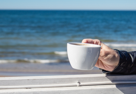 female hand holding a cup of coffee in an outdoor cafe near the sea on sunny day closeup