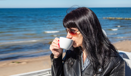 young brunette woman in black leather jacket and sunglasses drinking coffee in an  outdoor cafe near the sea on sunny day portrait closeup