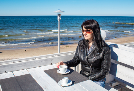 young brunette woman in black leather jacket and sunglasses drinking coffee in an  outdoor cafe near the sea on sunny day Stock Photo