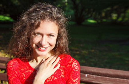 portrait of a young smiling beautiful spanish girl in red dress sitting onthe bench in the city park outdoor on sunny summer day