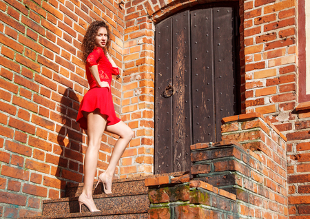 young woman in red dress is standing on the stairs near vintage wooden door on sunny summer day