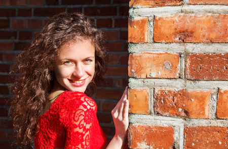 portrait of a young smiling beautiful spanish girl in red dress near the brick wall outdoor on sunny summer day