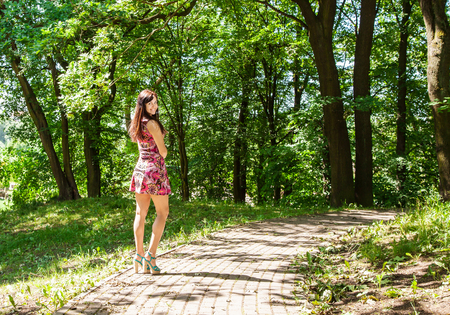 young beautiful woman in red dress standing on the alley in the park on bright sunny summer day Stock Photo