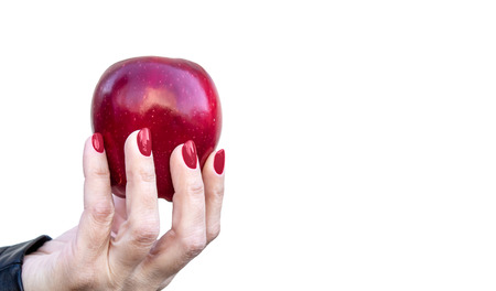 female hand holding a red apple isolated on white background closeup