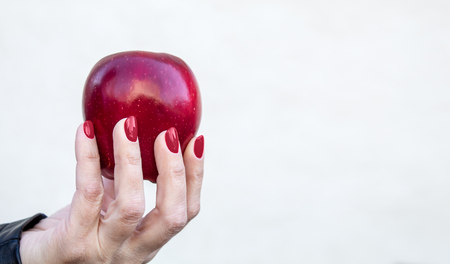 female hand holding a red apple on white background Stock Photo - 124976870