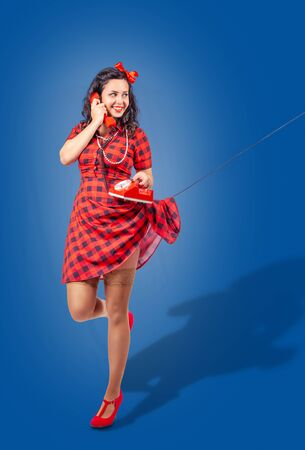 happy young pinup standing woman in red dress and nylon stockings talking  on phone over blue background