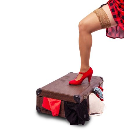 woman in red dress and nylon stockings standing her leg on a suitcase  isolated on white. legs closeup