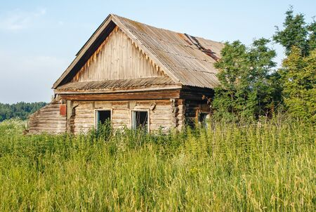 old abandoned wooden house in the russian village on summer day