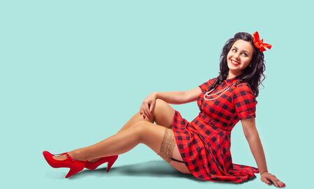young smiling pinup woman in red dress and nylon stockings sitting on the floor Standard-Bild
