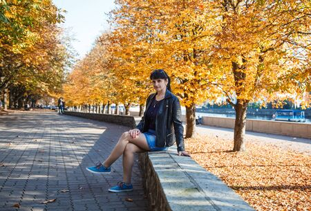 young brunette smiling woman on a walk in the park on sunny autumn day Reklamní fotografie