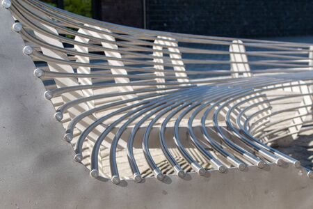 modern metal round garden bench in the city park on sunny summer day closeup