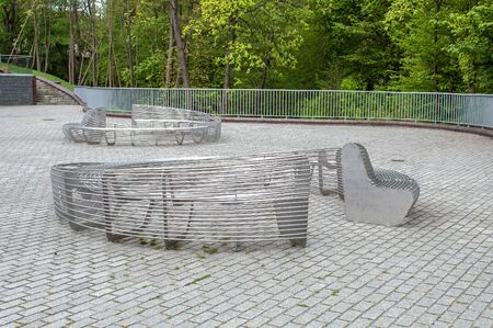 two modern metal round garden benches in the city park on sunny summer day