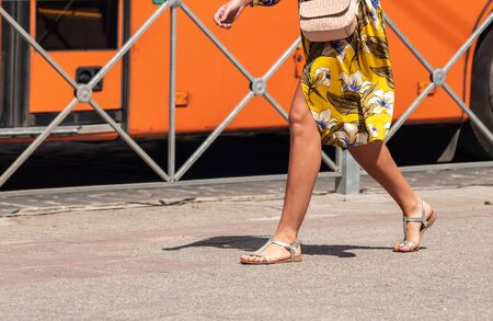 young woman in bright yellow dress walking down the street on sunny summer day