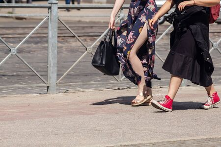 two young women in bright dresses walking down the street on sunny summer day