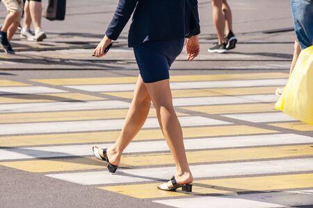 feet of pedestrians walking on the crosswalk on summer day